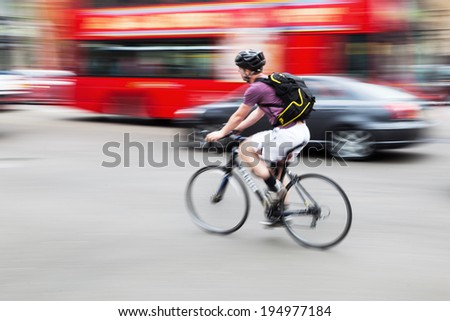 bicycle rider in London in motion blur with a blurred London bus in the background - stock photo