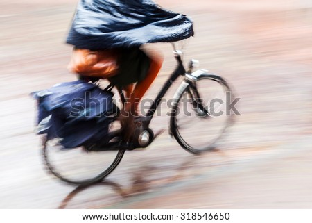bicycle rider in motion blur while it is raining - stock photo