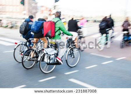 bicycle riders in the city traffic in motion blur - stock photo