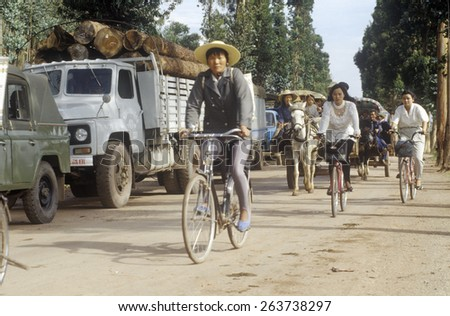 Bicycle riders passing by traffic jam on road to Kunming from Dali, Yunnan Province, People's Republic of China