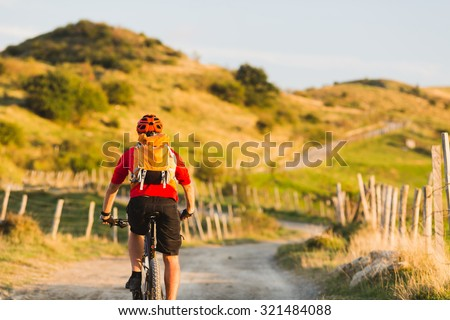 Bicycle riding enduro adventure in sunset summer mountains landscape. Man cycling MTB on rural country road. Sport fitness motivation and inspiration. - stock photo