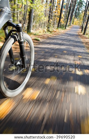 Bicycle riding on country road. Autumn scene. - stock photo