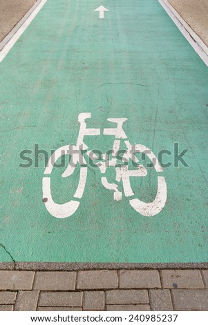 Bicycle road sign on green pavement