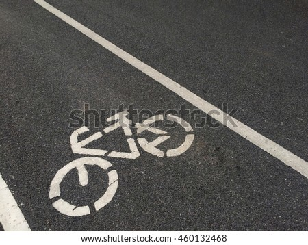 Bicycle road sign painted on pavement , asphalt road