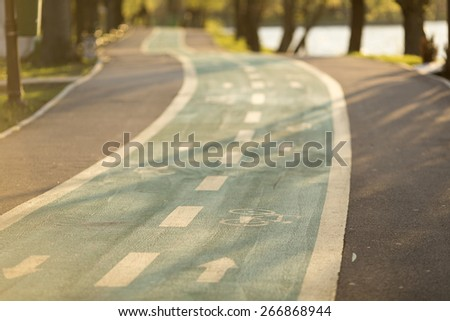 Bicycle road signs in a park on sunset - stock photo