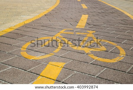Bicycle sign on a bending bikeway marked with yellow lines and dashed lane separator - stock photo