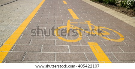Bicycle sign on a bikeway marked with yellow lines and dashed lane separator