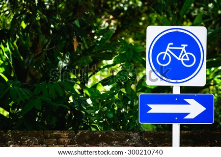 Bicycle sign post on the roadside with  green trees