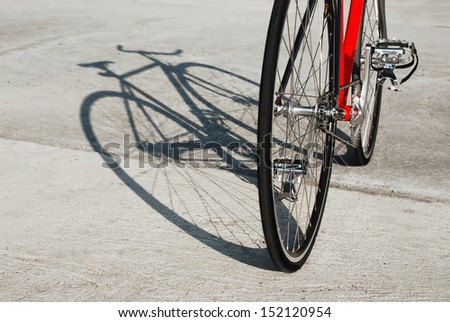 Bicycle standing in the parking lot and its shadow