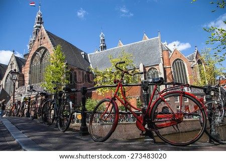 bicycle, symbol of Amsterdam, Netherlands in front of the Oude Kerk (Old Church) from across the Oudezijds Voorburgwal canal - stock photo