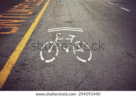 Bicycle symbol on city street. Bike sign on the road. Bike lane. Vintage effect. - stock photo