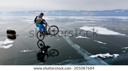 Bicycle tourist on the bike with sledge riding on the rear wheel only and having fun on the frozen lake - stock photo