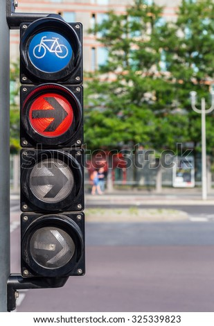 Bicycle traffic lights with red light and black arrow in the city on bright day.