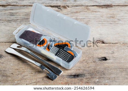 Bicycle tube repair kit in plastic box on wooden table - stock photo