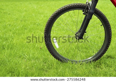 bicycle wheel on the pure green meadow with focus on wheel