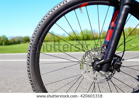 Bicycle wheel with disc hydraulic brakes. Blurred asphalt road and green grass on background