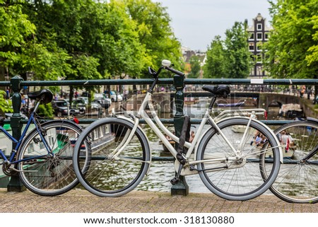 Bicycles on a bridge over the canals of Amsterdam, Netherlands in a summer day
