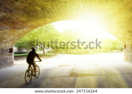 Bicycling in garden, Valencia. Cyclist is in motion blur! - stock photo