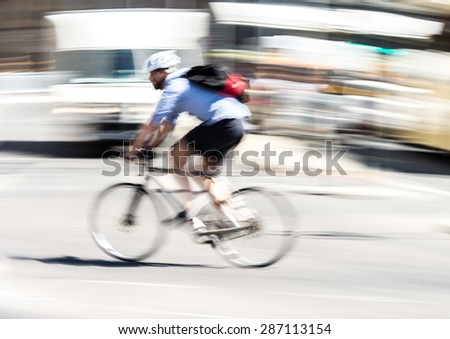 Bicyclist in city traffic  - stock photo