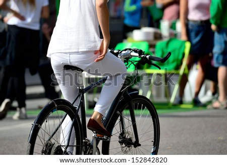 Bicyclist in traffic, woman in white