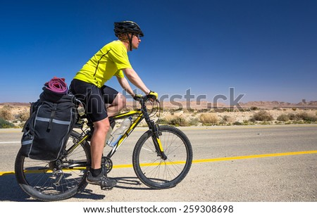 Bicyclist in yellow T-shirt rides on the road - stock photo