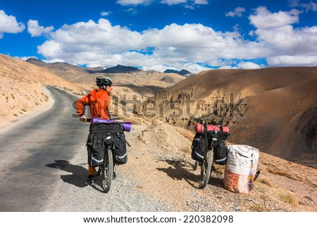 Bicyclist riding in fantastic landscape on mountain road, Jammu and Kashmir State, North India  - stock photo