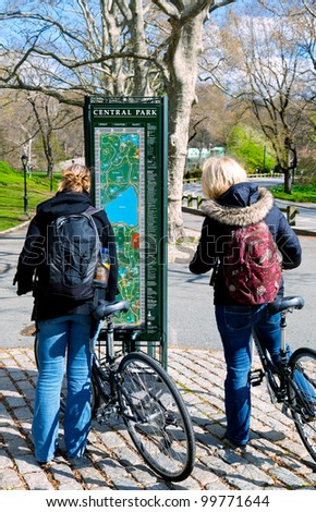 Bicyclists in Central Park, New York City, stop to check a map kiosk - stock photo