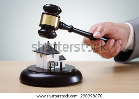 Bidding on a home, gavel and house concept for home ownership, buying, selling or foreclosure - stock photo