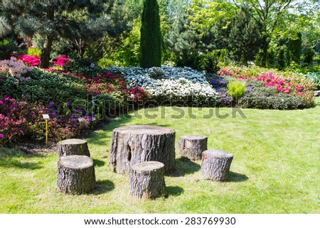 BIELSKO BIALA, POLAND - MAY 16: well kept garden with azalea and rhododendrons and old wood as table and chairs in Bielsko Biala, Poland on May 16, 2015.