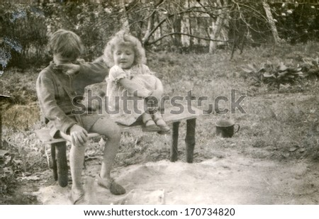 BIELSKO, POLAND, CIRCA FORTIES - vintage photo of brother and little sister on bench