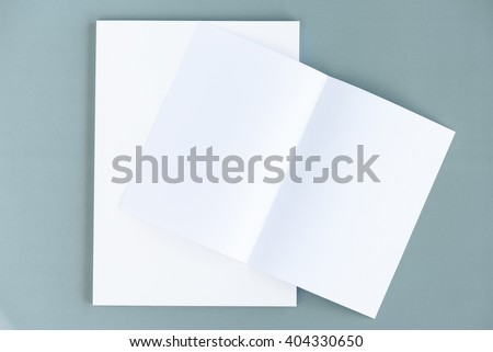 Bifold white template paper on a blank catalog, magazine, book mock up, opened with inside facing up. Isolated on grey cardboard, with clipping path included. Changeable background color and content. - stock photo