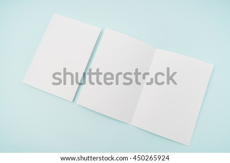 Bifold white template paper on blue background - stock photo