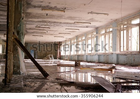 big abandoned hall with big broken windows, white  on the floor and puddles. - stock photo