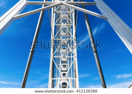 big abstract part of a design of a ferris wheel  from metal of white color against blue sky