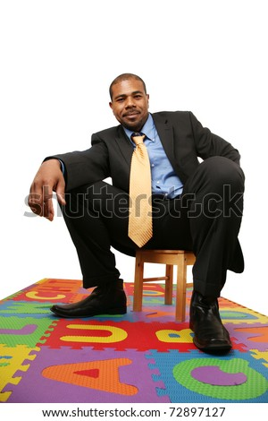 Big African American businessman sitting on small chair over white background. - stock photo