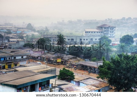 Big African city at dawn with typical tin roofs and people already out in the streets. - stock photo