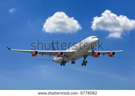 Big airliner and two white clouds on a blue sky - stock photo