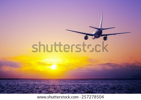 big airplane in the sky flying over ocean - stock photo