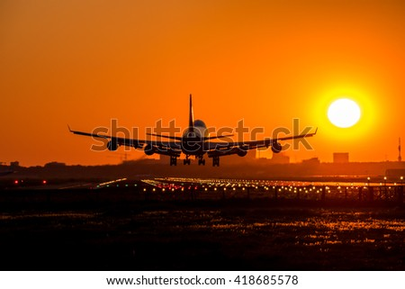 Big airplane is approaching the runway during sundown. - stock photo