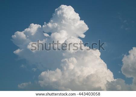 Big and fluffy cumulonimbus cloud in the blue sky - stock photo