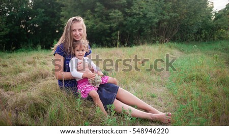 Big and little girls sit on grass and smile. Family walk on a wild glade