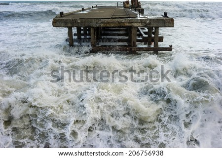 Big and powerful sea waves during the storm. Old ruined pier near the shore - stock photo