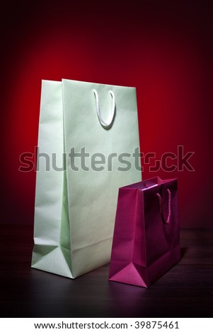 Big and small gift bags on wooden table top and nice color background - stock photo