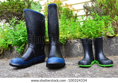 Big and small gumboots in the garden. - stock photo