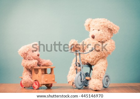 Big and small Teddy Bears on old retro toy bicycle and wooden car. Vintage instagram style filtered photo - stock photo