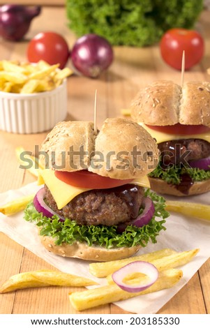 Big and tasty beef burger with cheese and vegetables.Selective focus on front burger  - stock photo