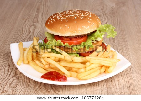 Big and tasty hamburger and fried potatoes on plate on wooden table