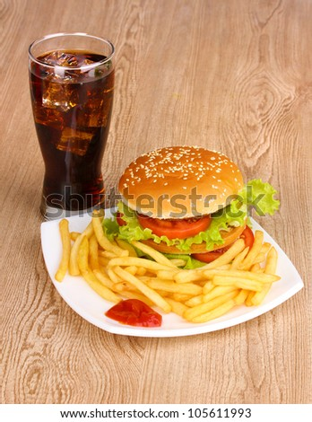 Big and tasty hamburger and fried potatoes on plate with cola on wooden table