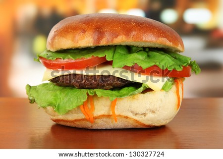 Big and tasty hamburger on table in cafe - stock photo