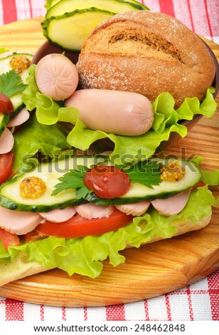 Big appetizing fast food baguette sandwich with lettuce, tomato and frankfurter on the board. Junk food - stock photo